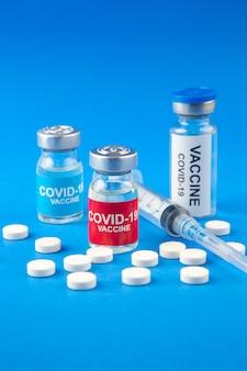 Vista frontal cercana de covid- vacunas en ampollas médicas píldoras jeringa desechable sobre fondo azul oscuro y suave