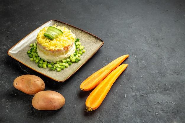 Vista frontal cercana de deliciosa ensalada servida con pepino picado y zanahorias con patatas sobre fondo oscuro