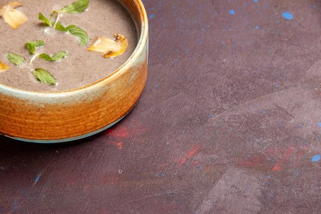 Vista frontal cercana deliciosa sopa de champiñones dentro de la placa en el espacio oscuro