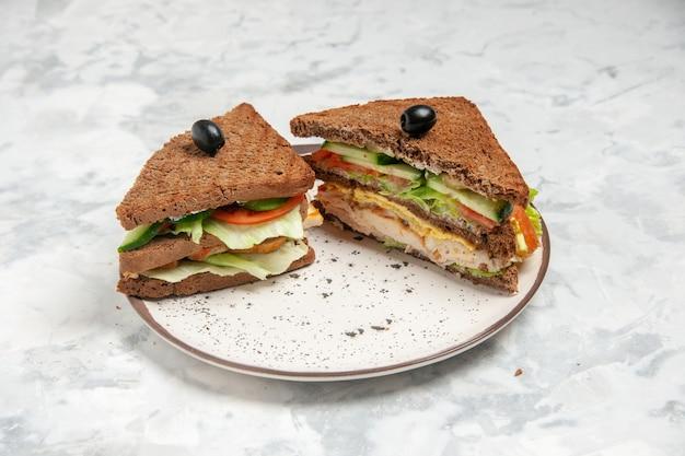 Vista frontal cercana del delicioso sándwich con pan negro decorado con oliva en un plato sobre la superficie blanca manchada