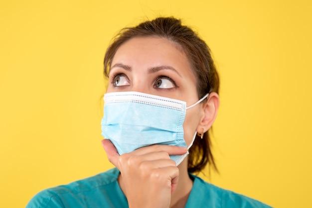 Vista frontal cercana doctora en máscara estéril sobre fondo amarillo