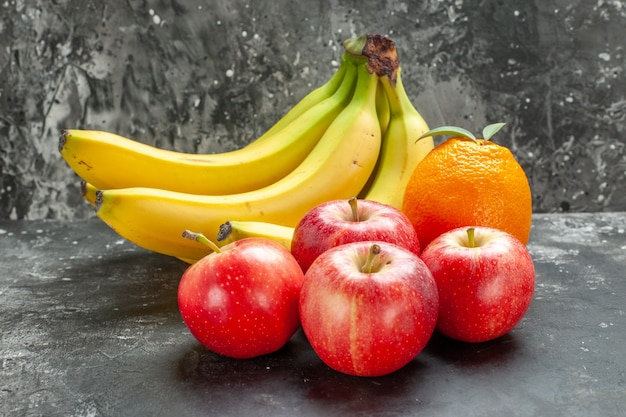 Vista frontal cercana de la fuente de nutrición orgánica paquete de plátanos frescos y manzanas rojas una naranja con tallo sobre fondo oscuro