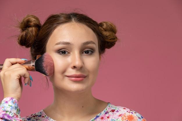 Vista frontal cercana joven en camisa diseñada con flores haciendo maquillaje en el fondo de color rosa