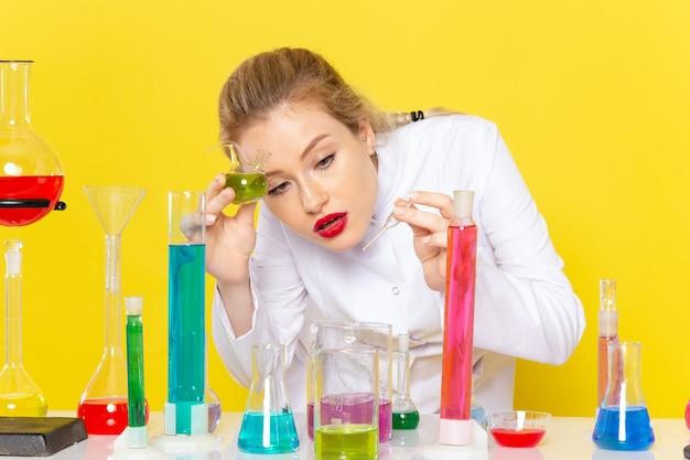Vista frontal cercana joven químico en traje blanco frente a la mesa con soluciones coloreadas en amarillo