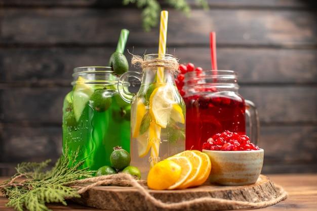 Vista frontal cercana de jugos frescos orgánicos en botellas servidas con tubos y frutas sobre una tabla de cortar de madera sobre una mesa marrón