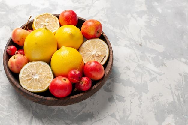 Vista frontal cercana limones frescos enteros y en rodajas en un espacio en blanco
