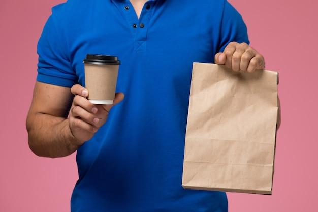 Vista frontal cercana mensajero masculino en uniforme azul con paquete de comida y taza de café en la entrega de trabajo de servicio uniforme rosa
