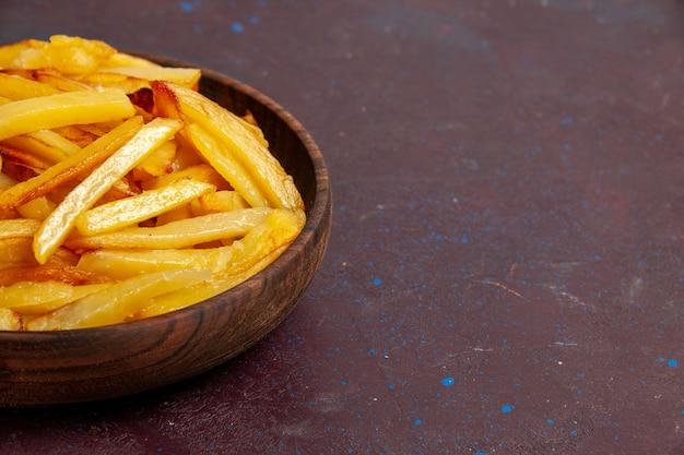 Vista frontal cercana patatas fritas sabrosas patatas fritas dentro de la placa en la superficie oscura comida cena ingredientes del plato patata