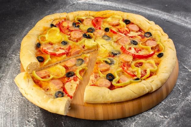 Vista frontal cercana sabrosa pizza cursi con tomates rojos, aceitunas negras y salchichas en la superficie oscura