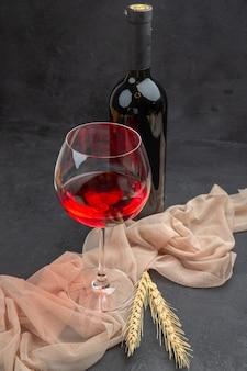 Vista frontal cercana de vino tinto en una copa de cristal sobre una toalla y botella sobre fondo negro