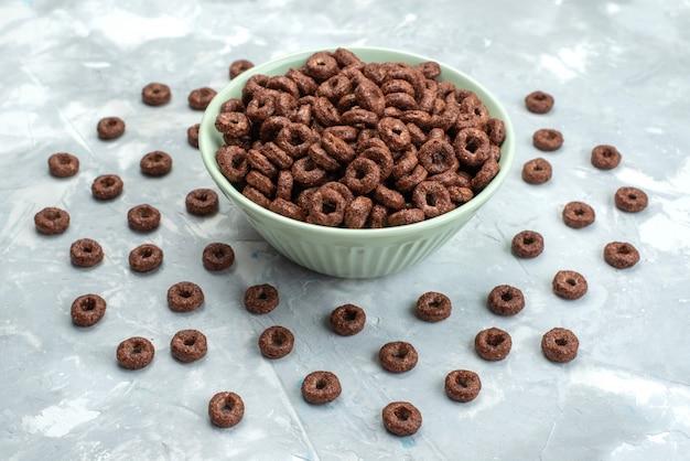 Vista frontal de los cereales de chocolate dentro de la placa verde sobre el fondo azul, cereales, alimentos para el desayuno de cacao, salud