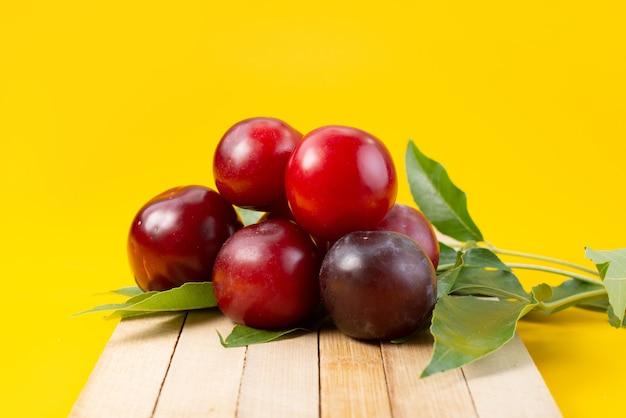 Una vista frontal de las cerezas rojas frescas suaves y ácidas sobre amarillo, color de verano de frutas