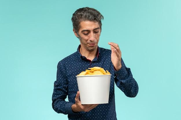 Vista frontal de la cesta de sujeción masculina de mediana edad con patatas cips en la superficie azul