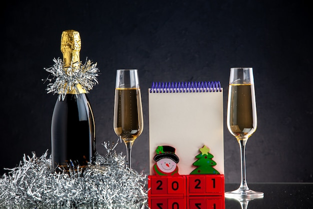 Vista frontal de champán en botella y vasos bloc de notas de bloques de madera sobre superficie oscura