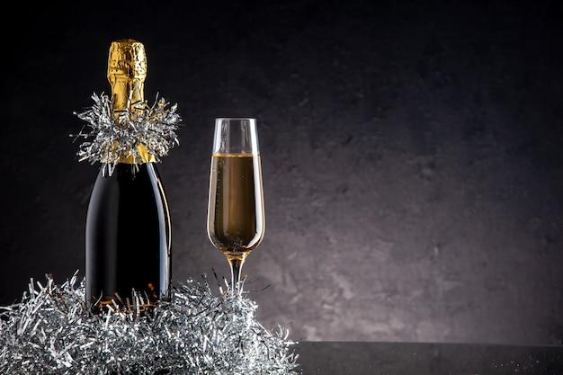 Vista frontal de champán en botella y vidrio sobre una superficie oscura