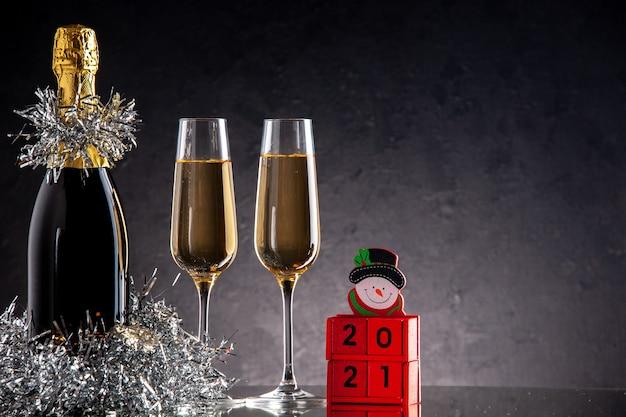 Vista frontal de champán en botellas y vasos de bloques de madera sobre una superficie oscura
