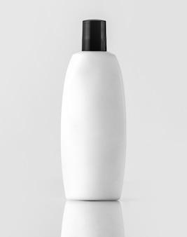 Una vista frontal champú embotellado blanco con tapa negra aislado en la pared blanca