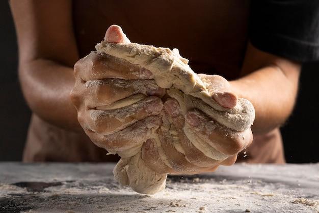 Vista frontal del chef amasando la masa en las manos