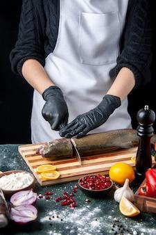 Vista frontal del chef cortar la cabeza de pescado en una tabla de cortar, molinillo de pimienta, tazón de harina, semillas de granada en un tazón en la mesa de la cocina