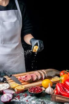 Vista frontal del chef exprimiendo limón en rebanadas de pescado cuchillo en tabla de cortar verduras en tabla de servir de madera en la mesa de la cocina