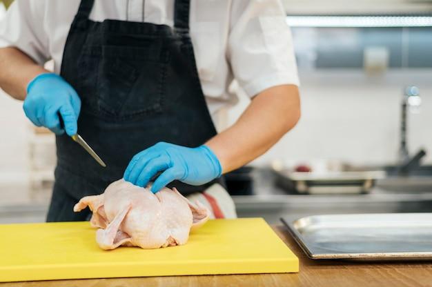 Vista frontal del chef con guantes cortando pollo