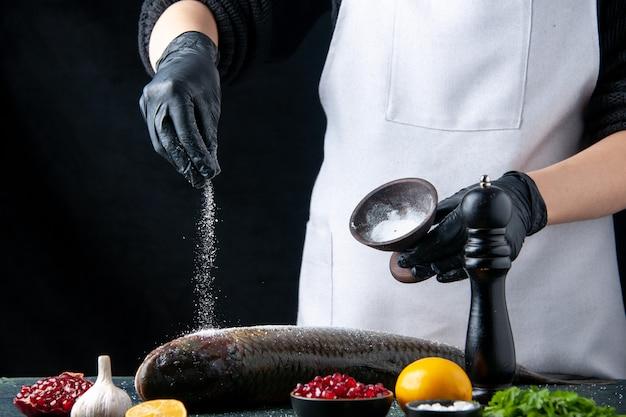 Vista frontal del chef con guantes espolvoreados con sal sobre semillas de granada de pescado fresco en un recipiente sobre la mesa