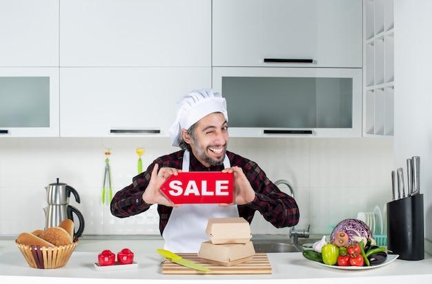 Vista frontal del chef macho parpadeando ojo sosteniendo cartel de venta en la cocina