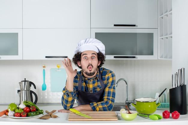 Vista frontal del chef masculino cocinando verduras frescas mostrando cinco en la cocina blanca