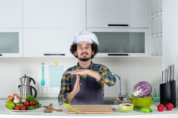 Vista frontal del chef masculino confiado con verduras frescas y cocinar con utensilios de cocina y hacer gesto de parada en la cocina blanca