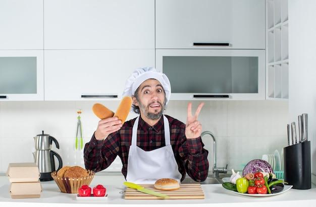 Vista frontal del chef masculino haciendo el signo de la victoria sosteniendo pan en la cocina