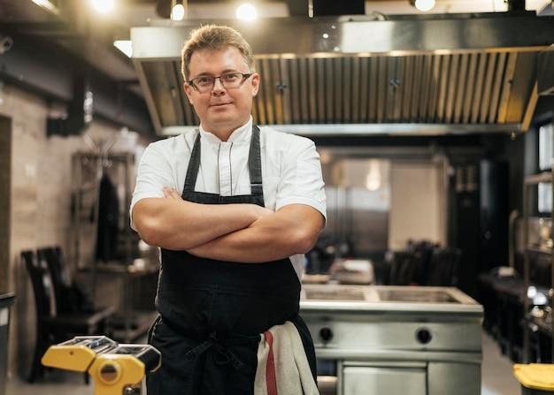 Vista frontal del chef masculino posando con los brazos cruzados en la cocina