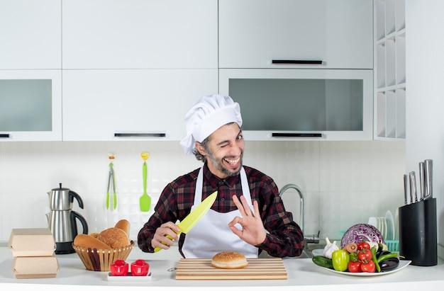 Vista frontal del chef masculino sosteniendo un cuchillo amarillo haciendo okey firmar en la cocina