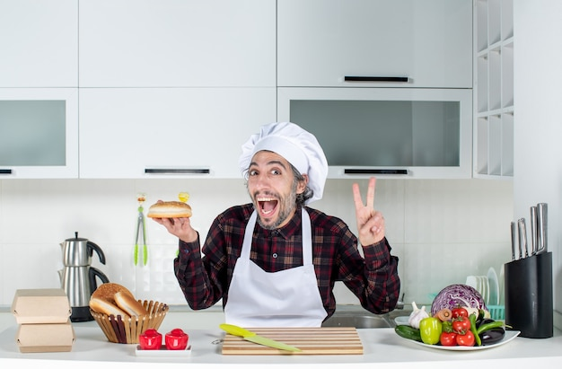 Vista frontal del chef masculino sosteniendo pan haciendo el signo de la victoria en la cocina