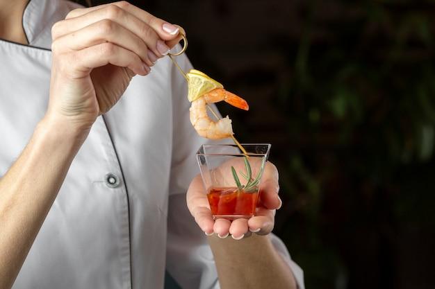 Vista frontal del chef con una receta de camarones