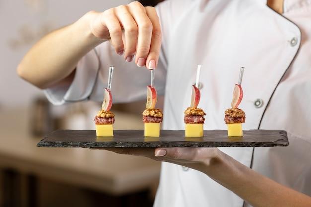 Vista frontal del chef sosteniendo un delicioso plato de comida