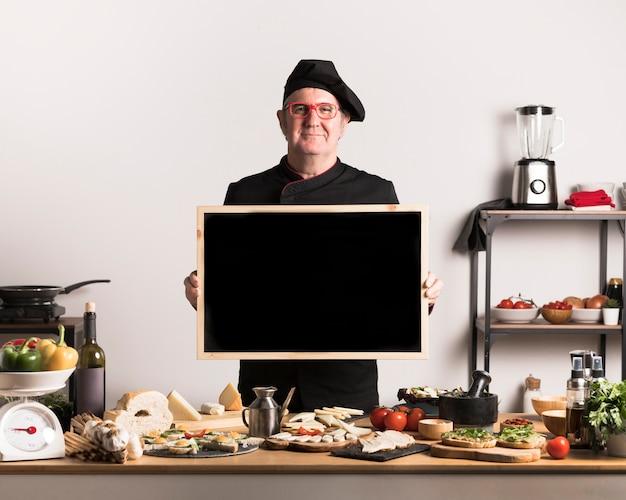 Vista frontal chef sosteniendo marco en blanco
