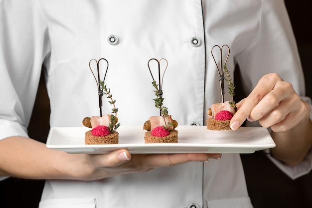 Vista frontal del chef sosteniendo un plato de comida