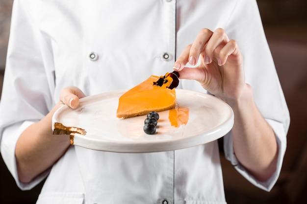 Vista frontal del chef sosteniendo un plato con pastel