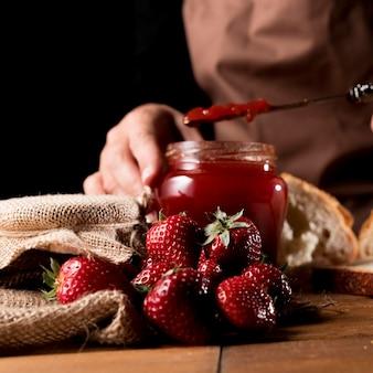 Vista frontal del chef con tarro de mermelada de fresa