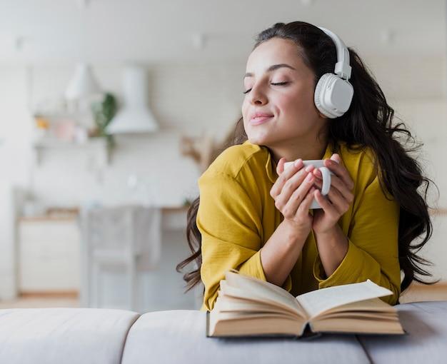 Vista frontal chica con auriculares y libro