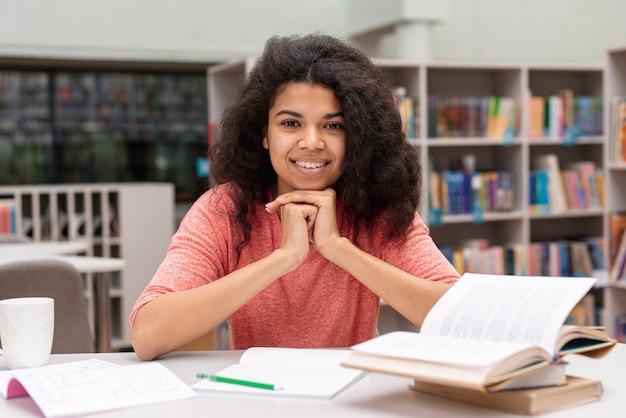 Vista frontal chica en la biblioteca estudiando