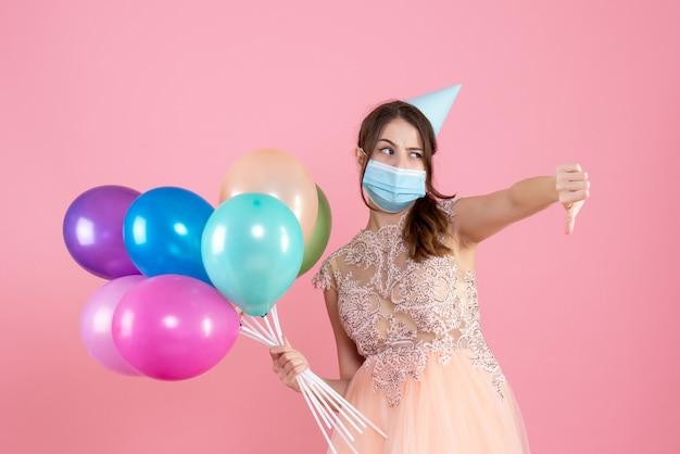 Vista frontal chica confundida con gorro de fiesta y máscara médica haciendo cartel con el pulgar hacia abajo sosteniendo globos de colores