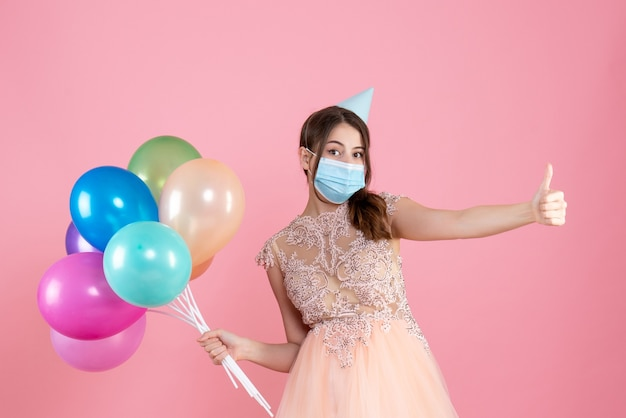 Vista frontal chica confundida con gorro de fiesta y máscara médica haciendo pulgar arriba cartel sosteniendo globos de colores