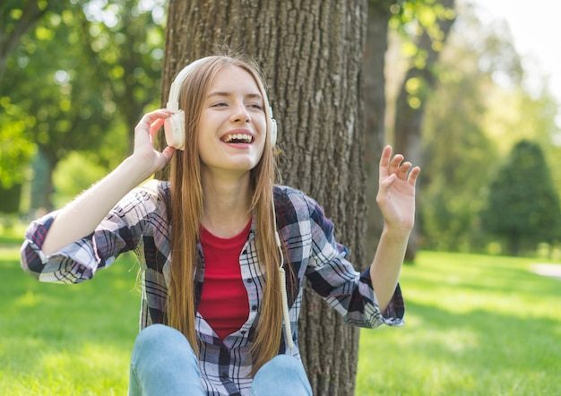 Vista frontal chica escuchando música al aire libre