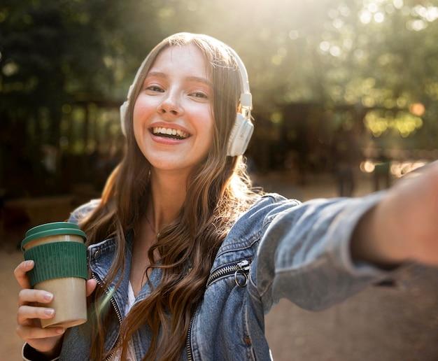 Vista frontal chica escuchando música en los auriculares