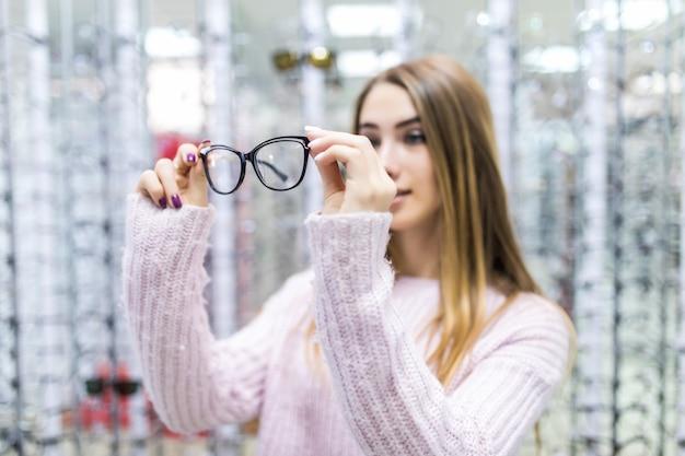Vista frontal de la chica guapa en suéter blanco, pruebe las gafas en la tienda