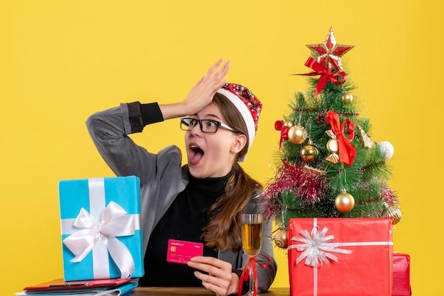 Vista frontal de la chica de ojos abiertos con sombrero de navidad sentado en la mesa poniendo la mano
