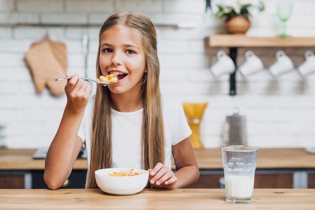 Vista frontal chica rubia comiendo sus cereales