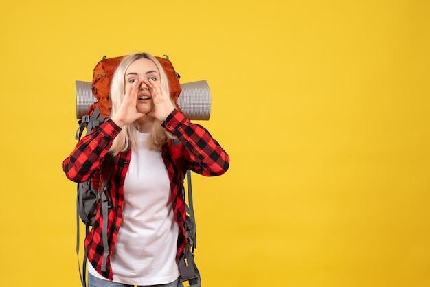 Vista frontal chica rubia con su mochila llamando a alguien