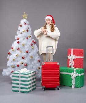Vista frontal chica sosteniendo valija con santa pidiendo tiempo sombrero